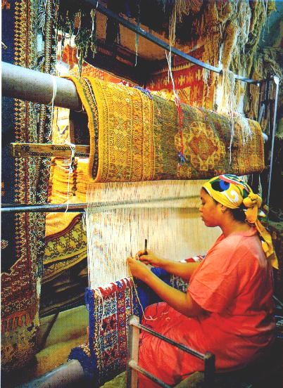 woman, traditionally weaving a carpet